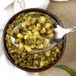 a spoonful of indian spiced beans with mustard seeds and sprouts