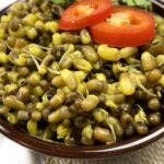 cooked beans with sprouts and red chili peppers that is indian spiced with turmeric and salt in a brown bowl.