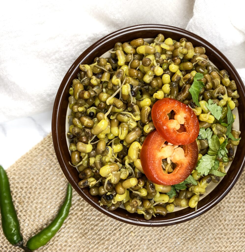 mung beans in a brown bowl with red chili peppers on top and green chili peppers on a mat