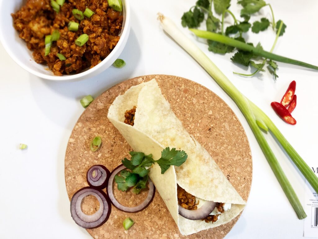 indian ground chicken wrapped in a siete tortilla on a brown hot plate with cilantro and onions