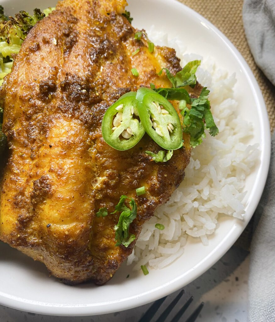 cooked tandoori fish in a plate with serano chilies on top