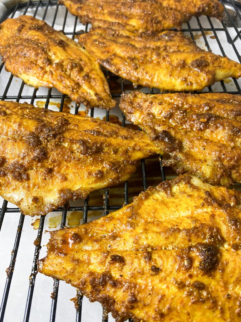 baked catfish in an oven with spices