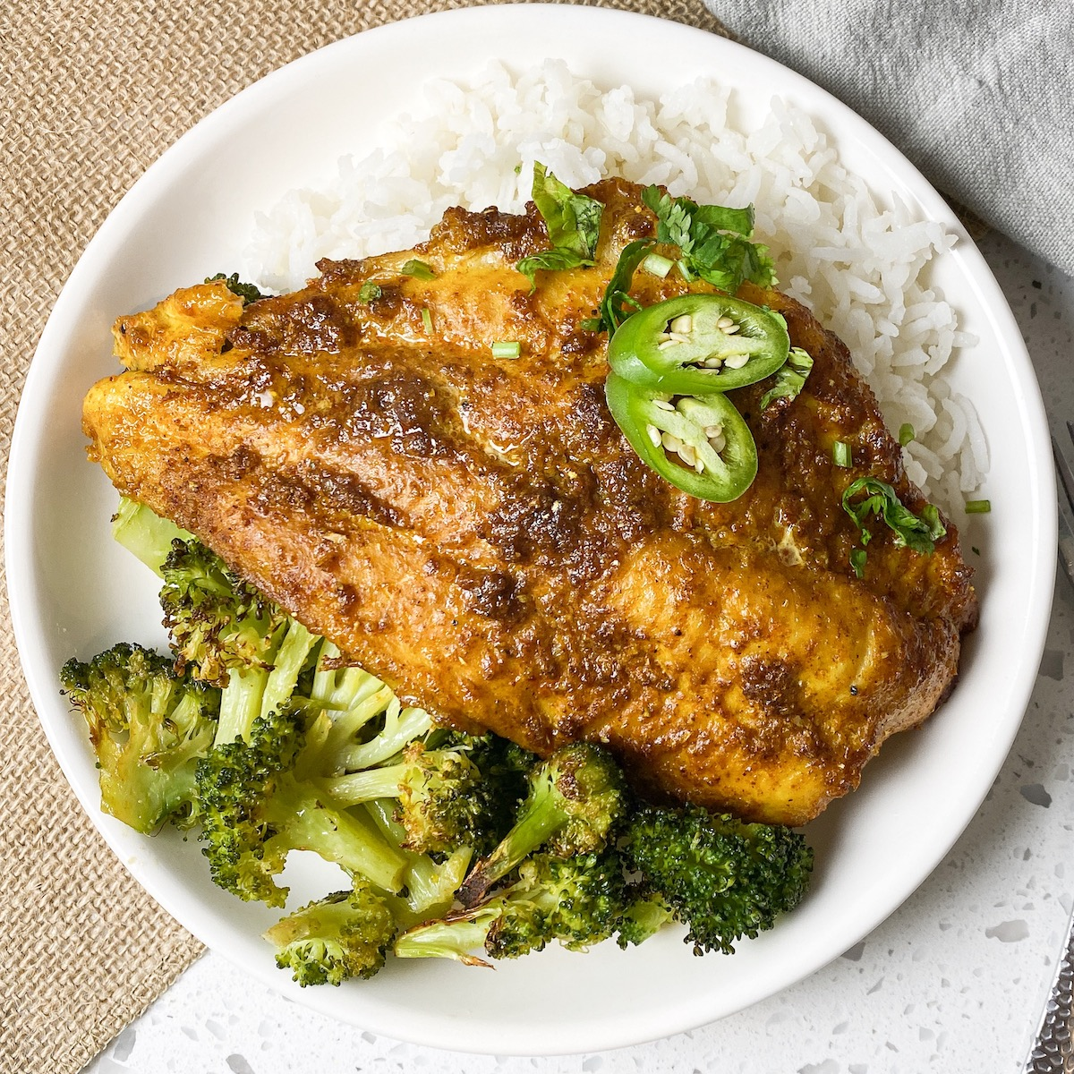 a round bowl with rice, cooked broccoli, and a oven baked indian catfish