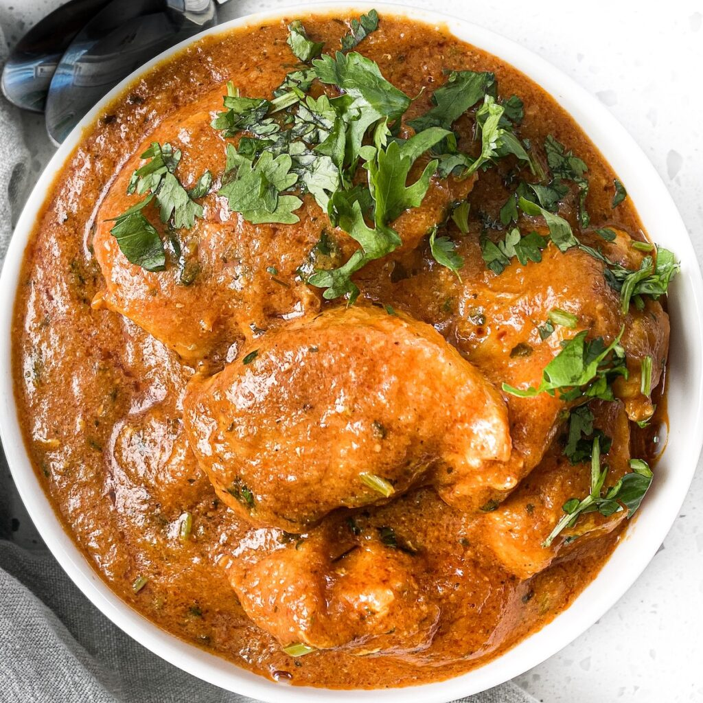 a round bowl with chicken tikka masala and cilantro on top