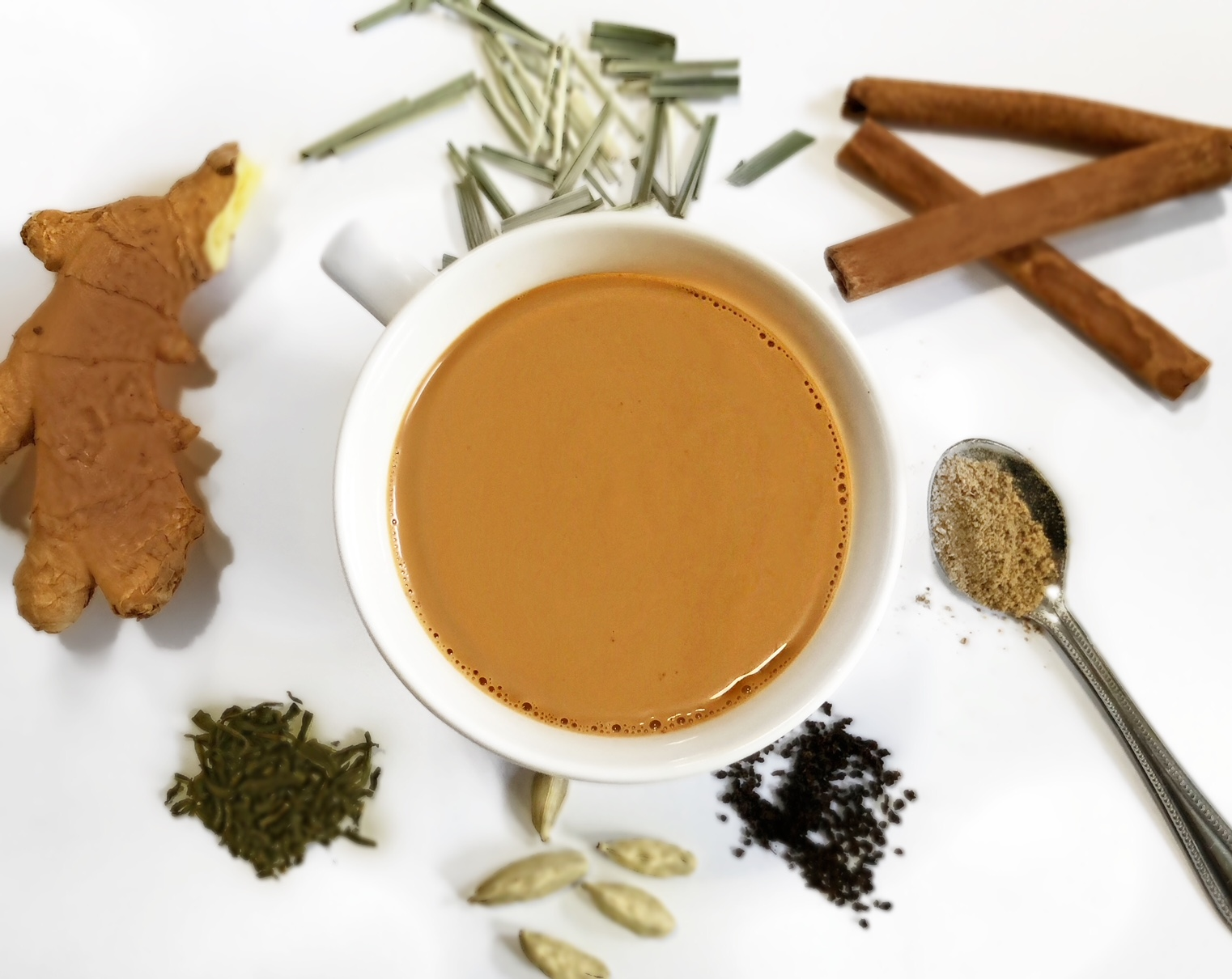 an authentic cup of chai or milk tea surrounded by spices and ginger root.