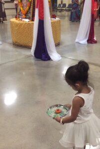 little girl holding an aarti dish