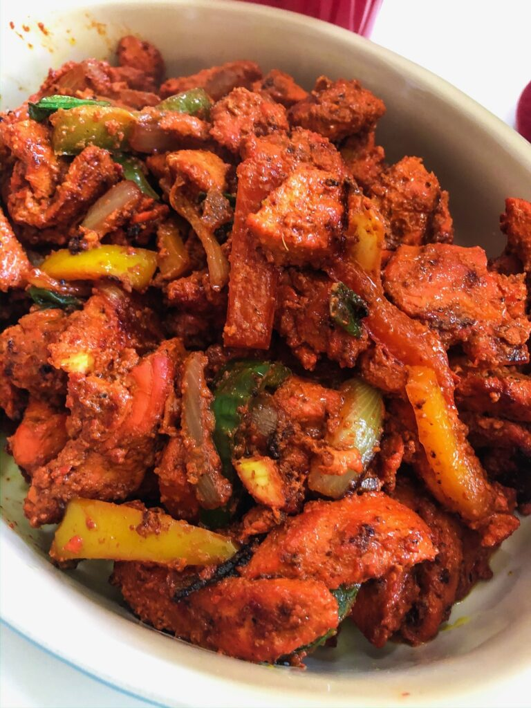 boneless tandoori chicken bright red in color with peppers and onions