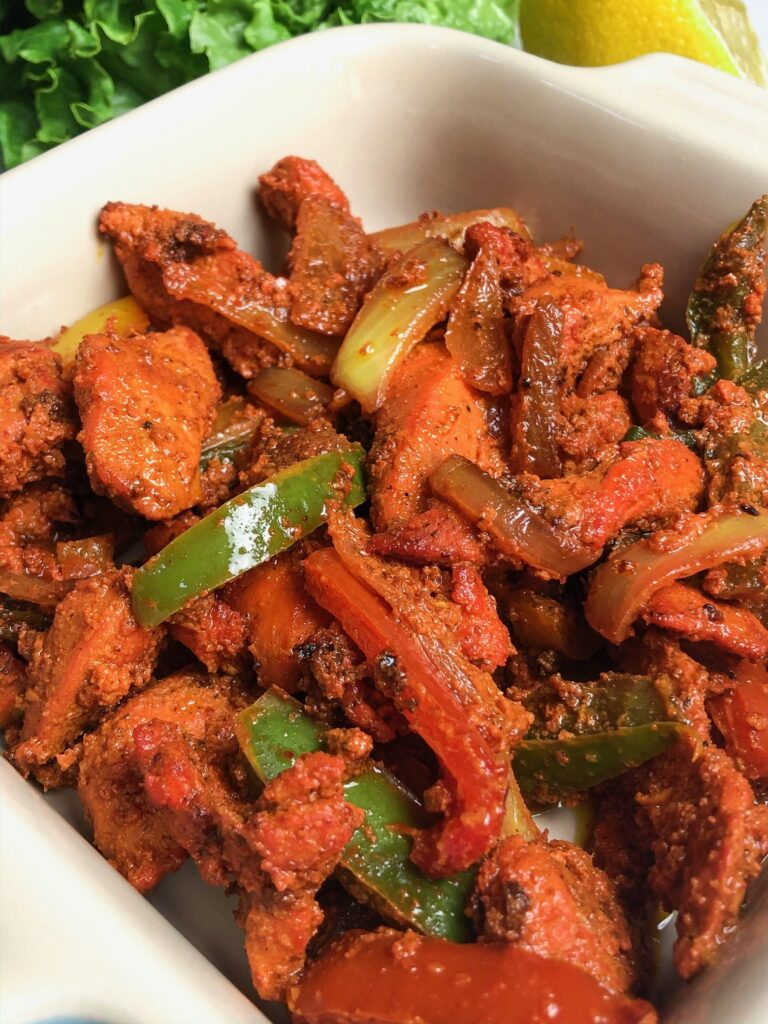 Boneless Tandoori Chicken with spices, turmeric, bell peppers, and onions.