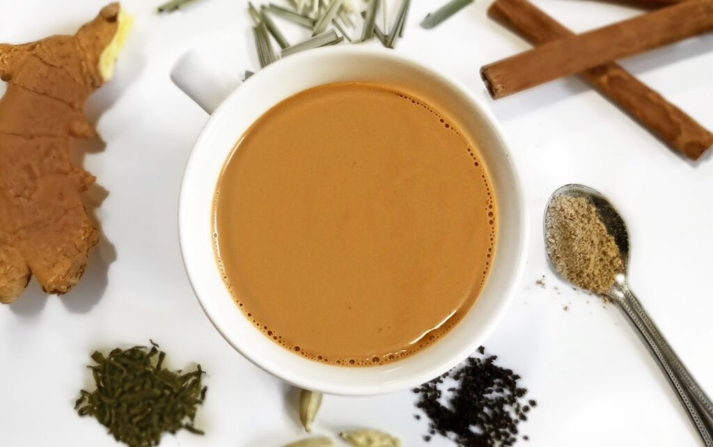 chai recipe round cup with spices around it