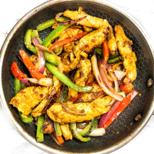 tandoori chicken with red and green peppers in a hexclad pan
