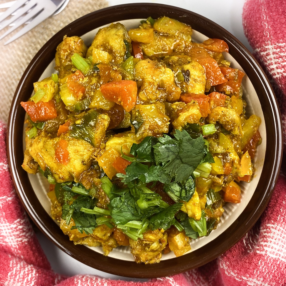 Bell Pepper chicken curry in a bowl with cilantro on one side