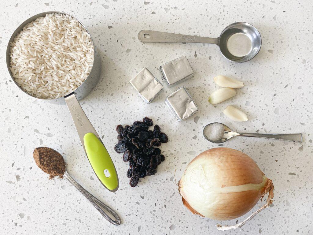masala rice ingredients layed out. Includes rice, onion, raisins, garam masala, bouillon, oil, salt, and garlic