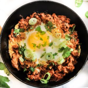 shakshuka with meat chicken and eggs indian breakfast in a bowl with runny egg
