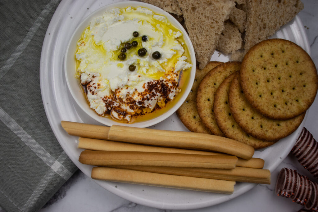 a yogurt dip with spicy pepper on top and crackers next to it