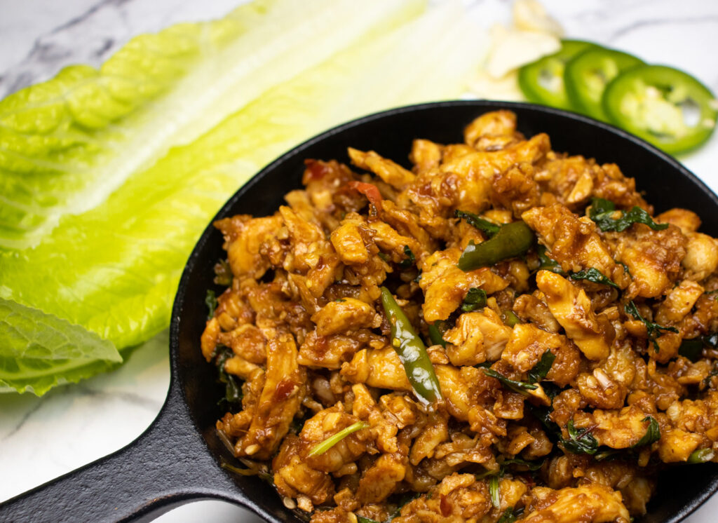 asian fusion minced meat chicken dish with thai basil in a cast iron pan and jalapenos on the side