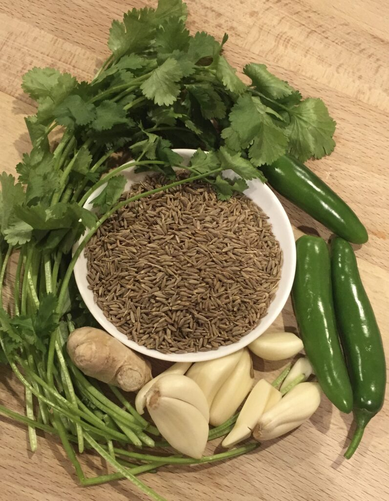 chutney ingredients for zhoug sauce. cilantro, cumin seeds, garlic, ginger, and chili peppers in a picture.