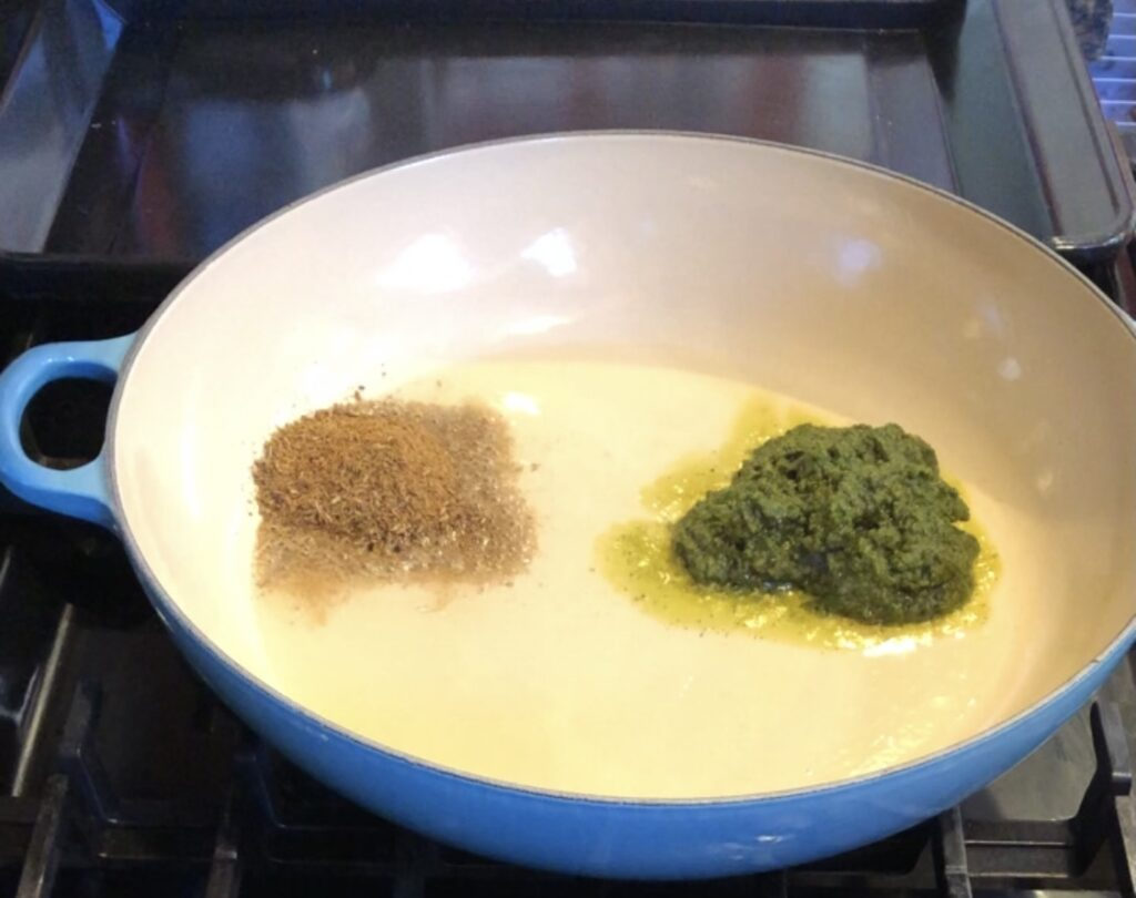 cumin seeds and zhoug sauce in a pan