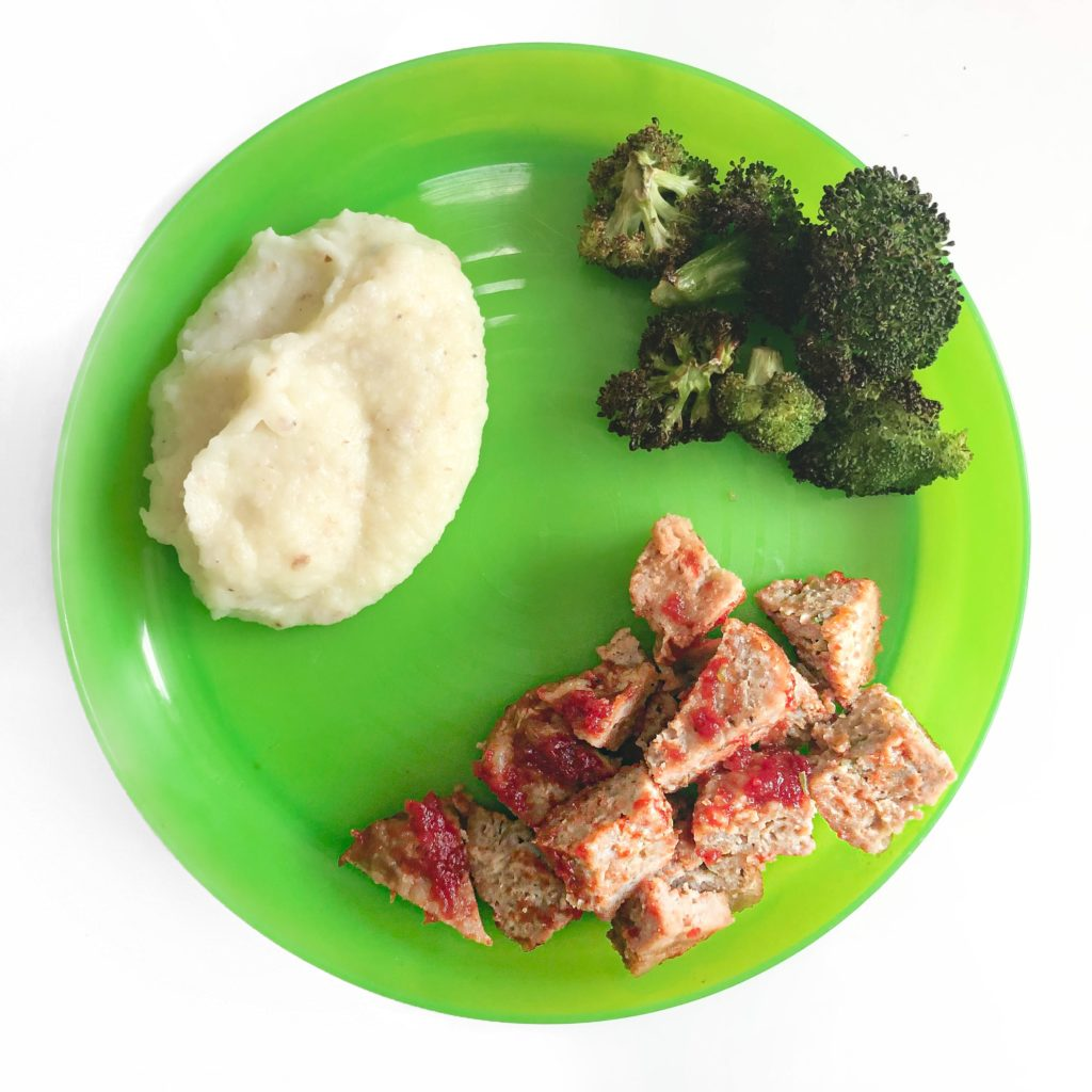 green kid plate with broccoli, mash, and meatlof