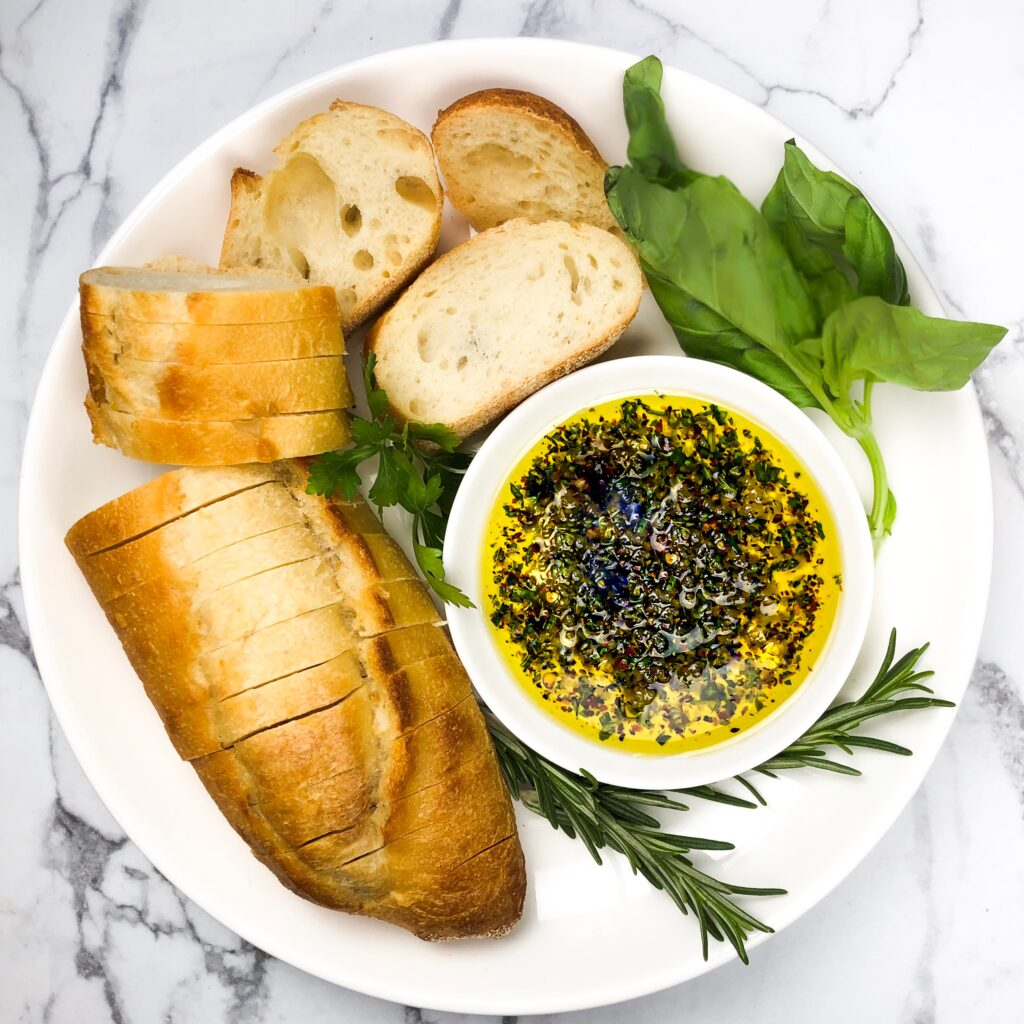 a round plate with bread and oil with fresh herbs that are dark green and bright red pepper flakes.
