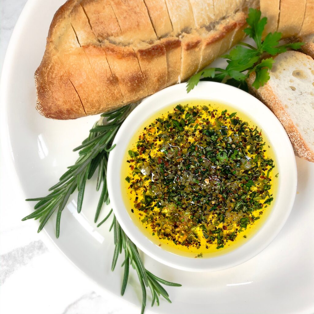 fresh herbs, bread, and a small plate with oil and herbs for dipping