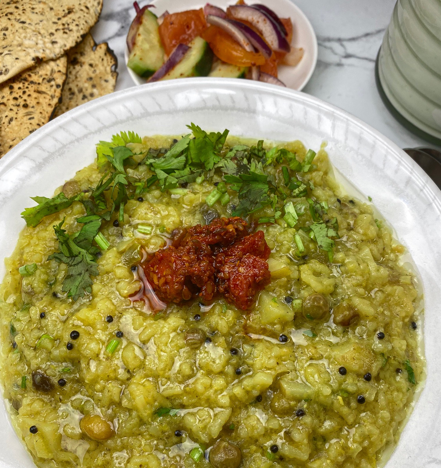 A slow cooked Gujarati porridge with rice, lentils, vegetables, and spices.