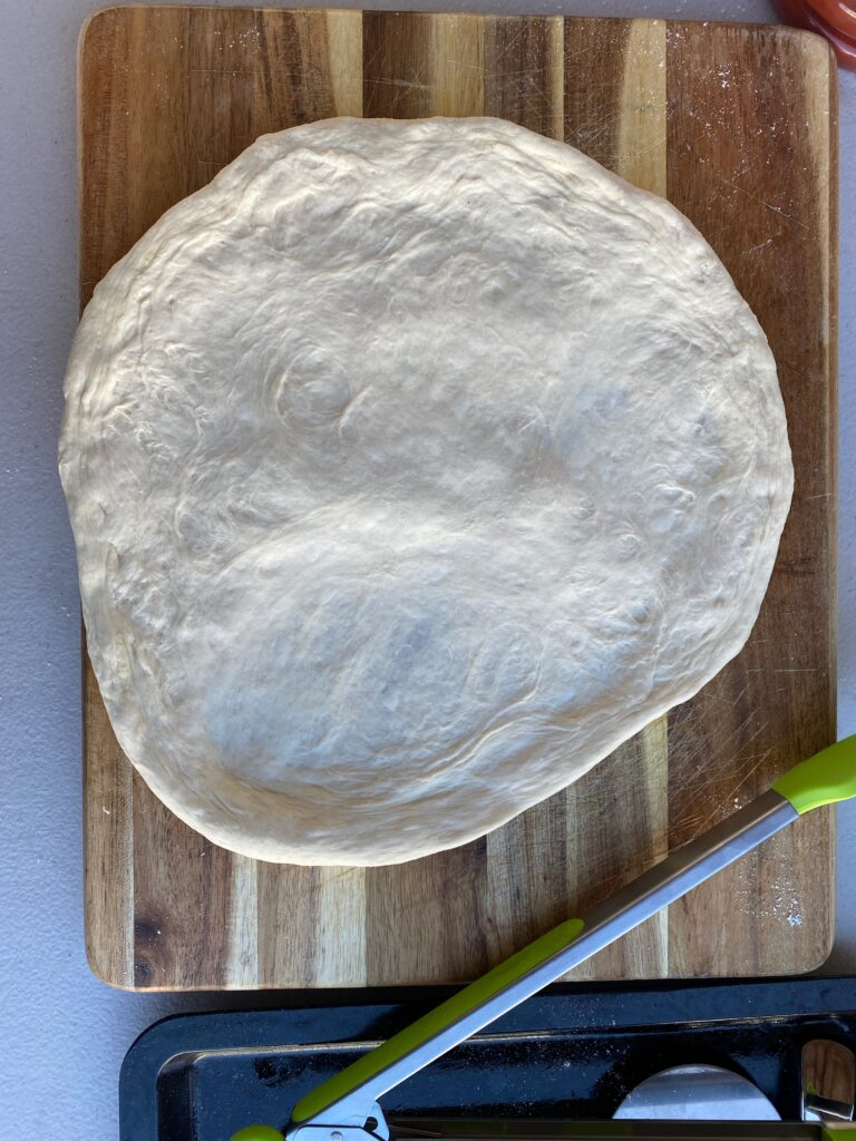 A hand stretched pizza dough laying on top of a cutting board