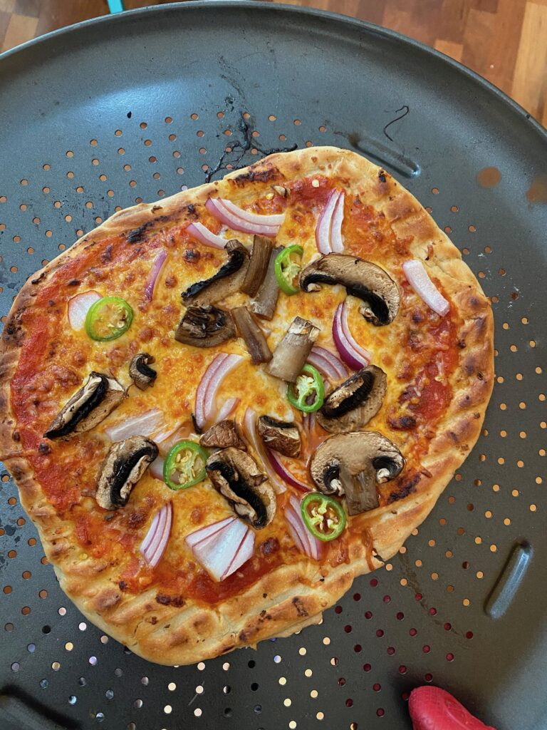A pizza with mushrooms onions and green chili peppers