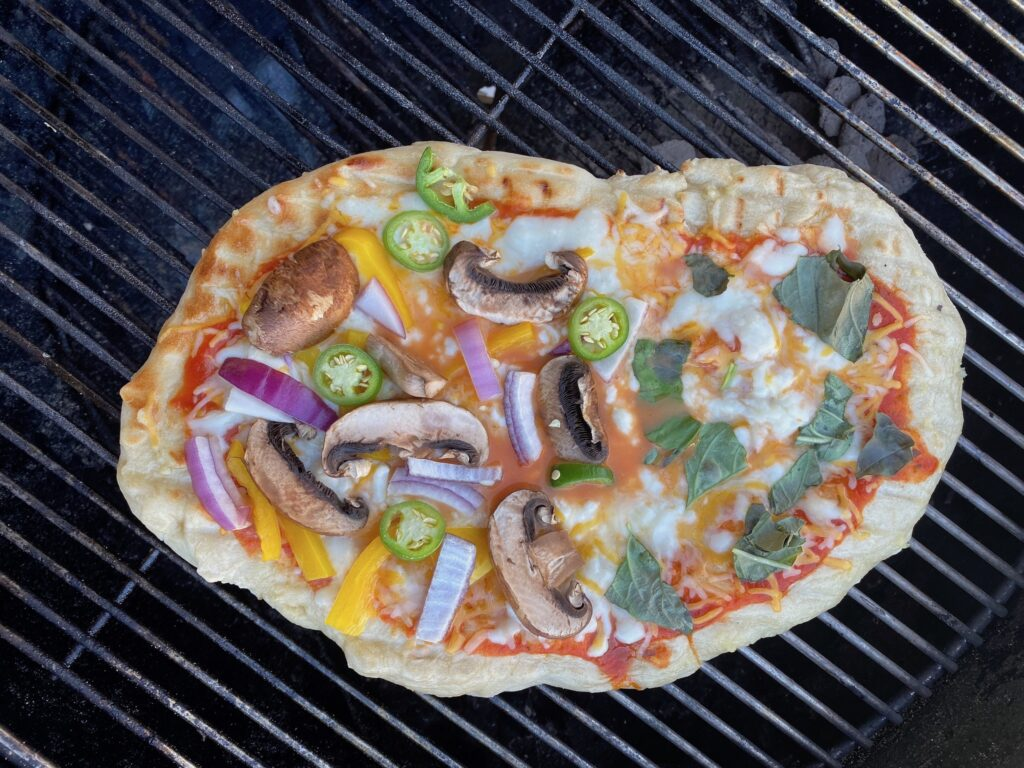 A pizza being grilled on a charcoal grillw ith msuhrooms onions and green chili peppers.