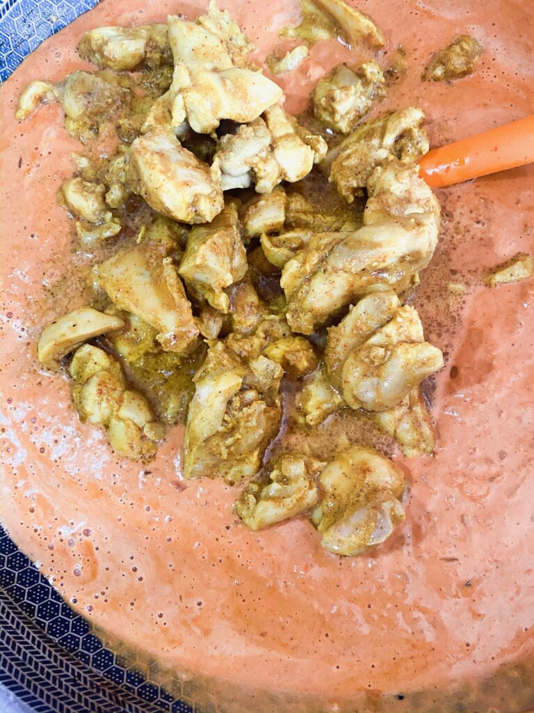 A mixture of cooked chicken that is being mixed with Chicken Tikka Masala sauce.