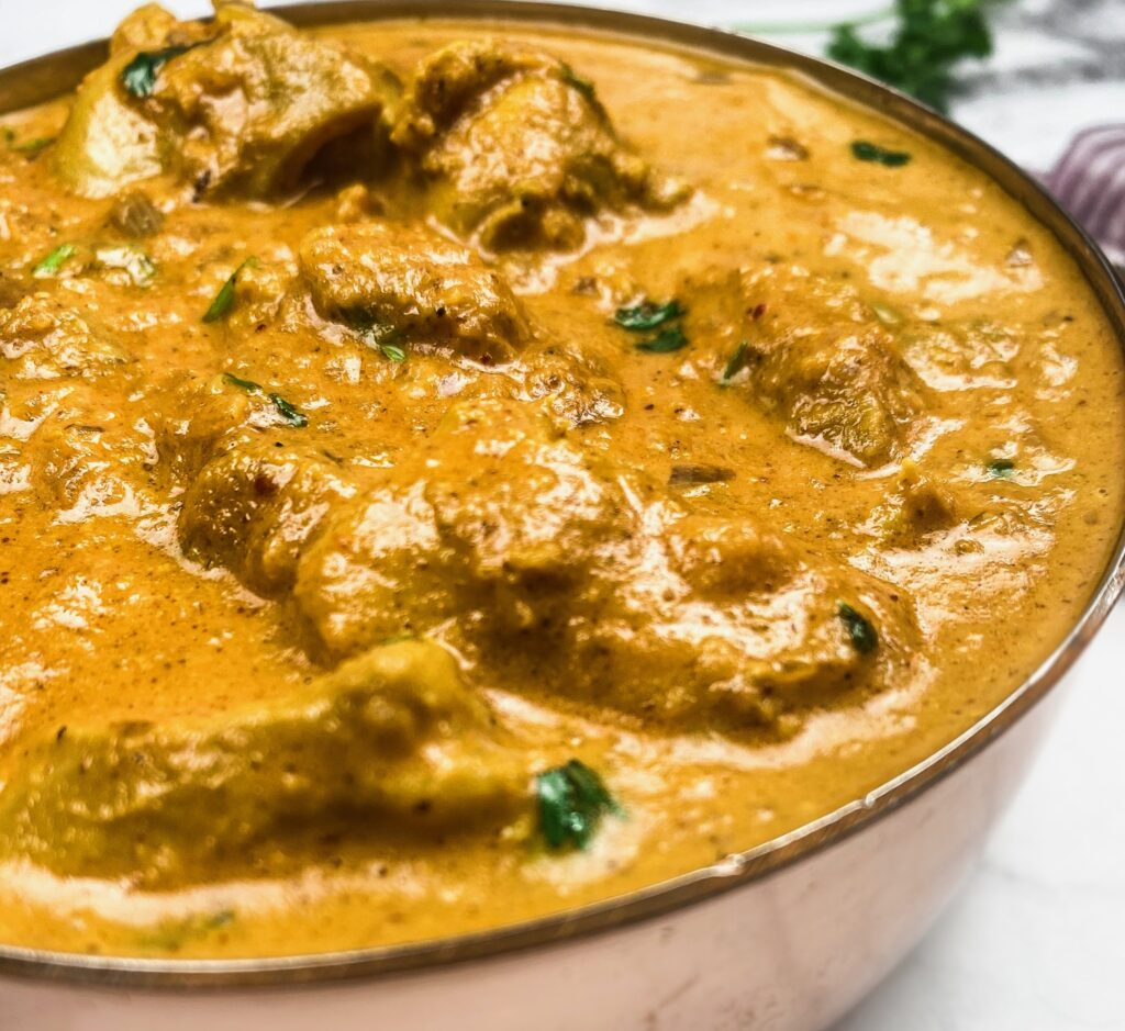 A pot of chicken tikka masala that includes chicken and a creamy sauce.