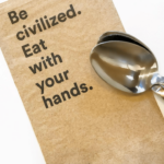 A napkin with the words Be civilized eat with your hands.
