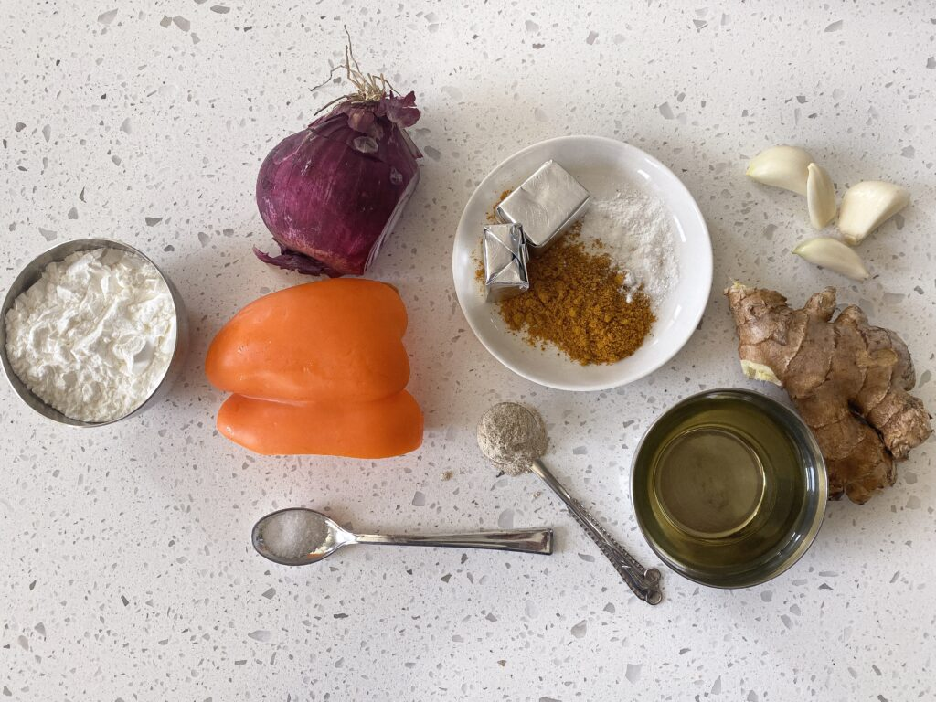 Ingredients for indo chinese chicken curry layed out bell pepper, onion, curry powder, corn starch, oil, and spices