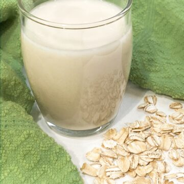 homemade oatmilk with a green cloth behind it and rolled oats in front