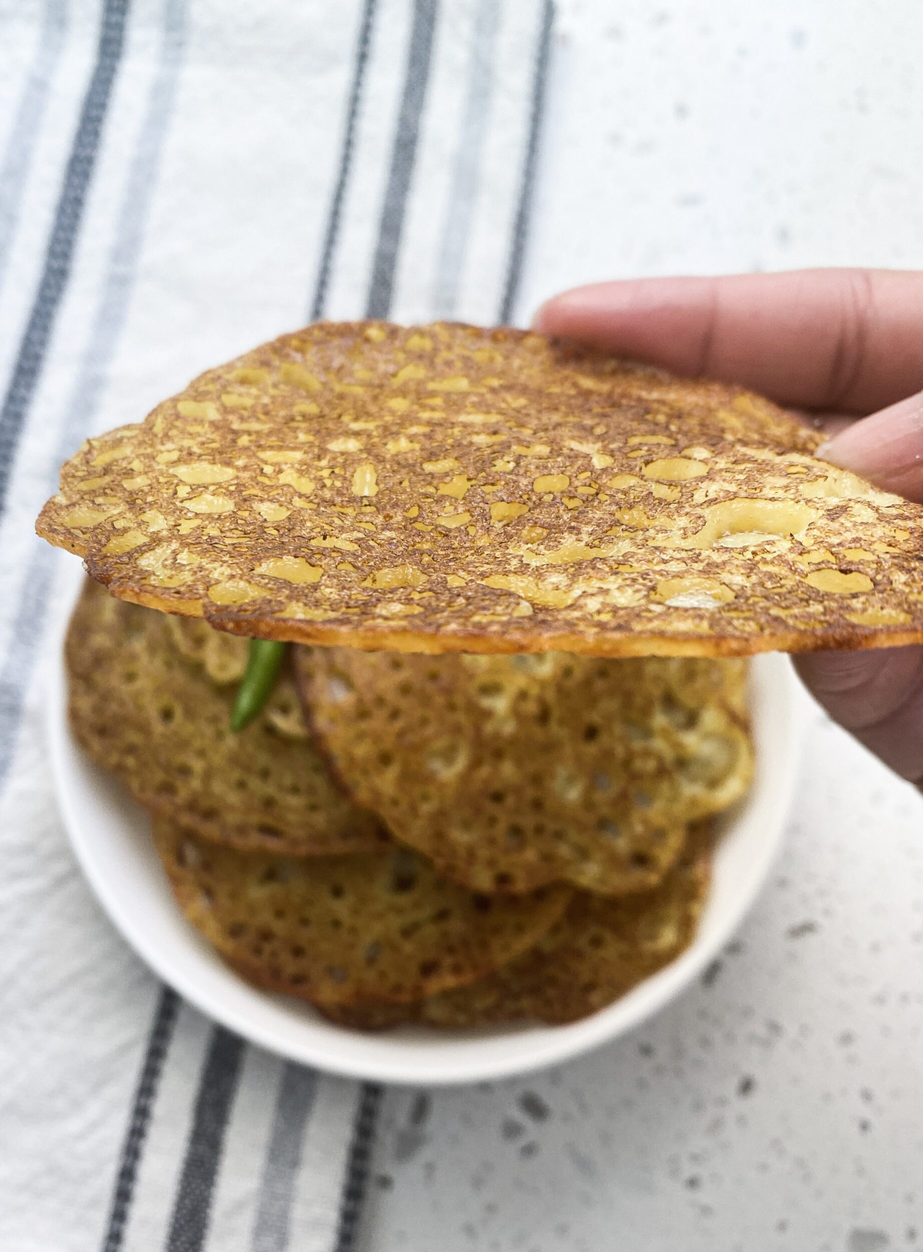 holding a flat khatta poodla with a hand showing thin and crisp end result