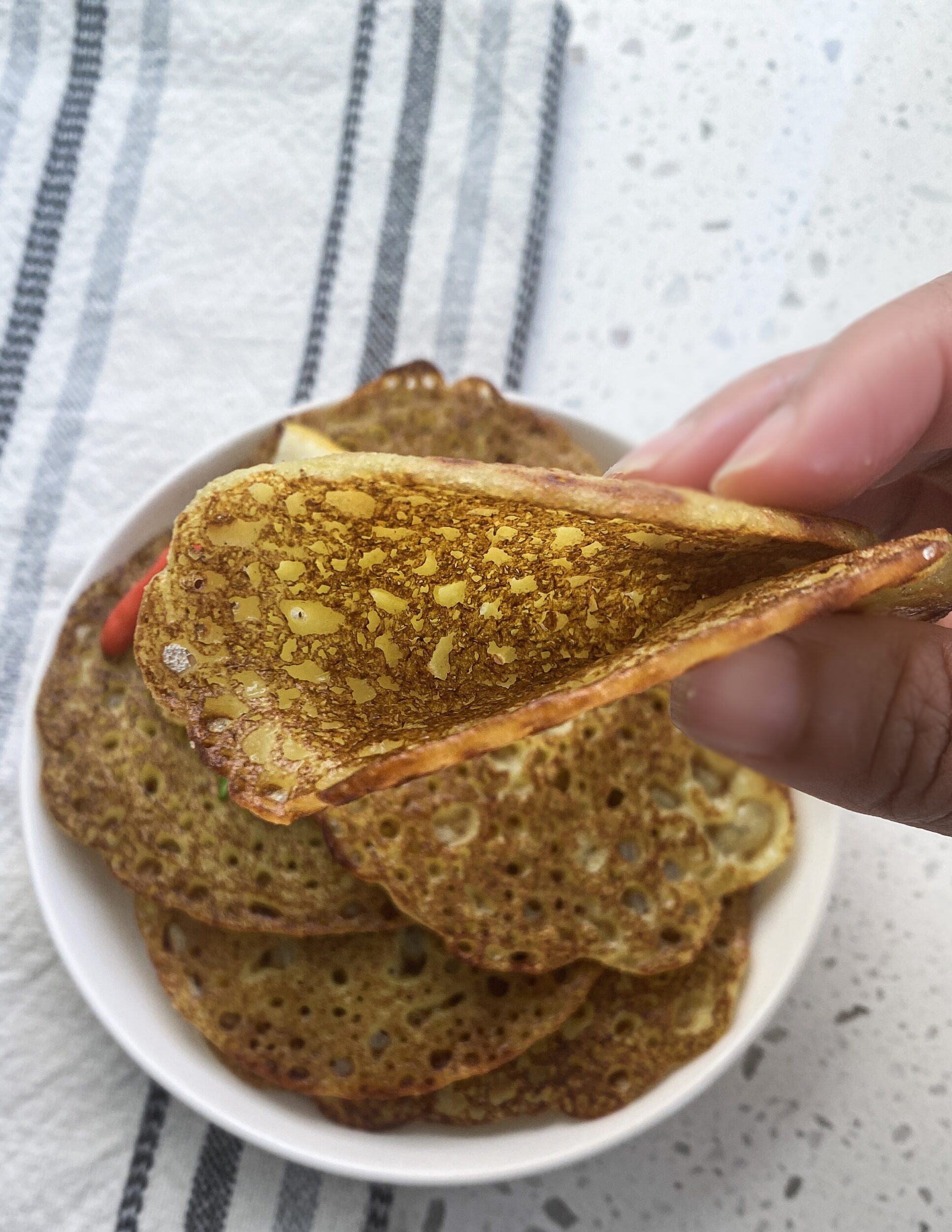 grandma's recipe for khatta puda folded in half to show crisp, thin, and soft texture