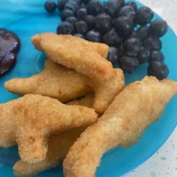 blue plate with blueberries and crispy chicken nuggets and bbq sauce
