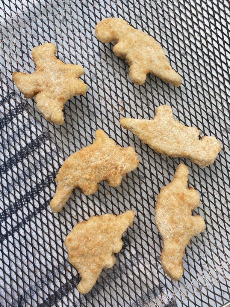 frozen dinosaur nuggets on a air fryer basket
