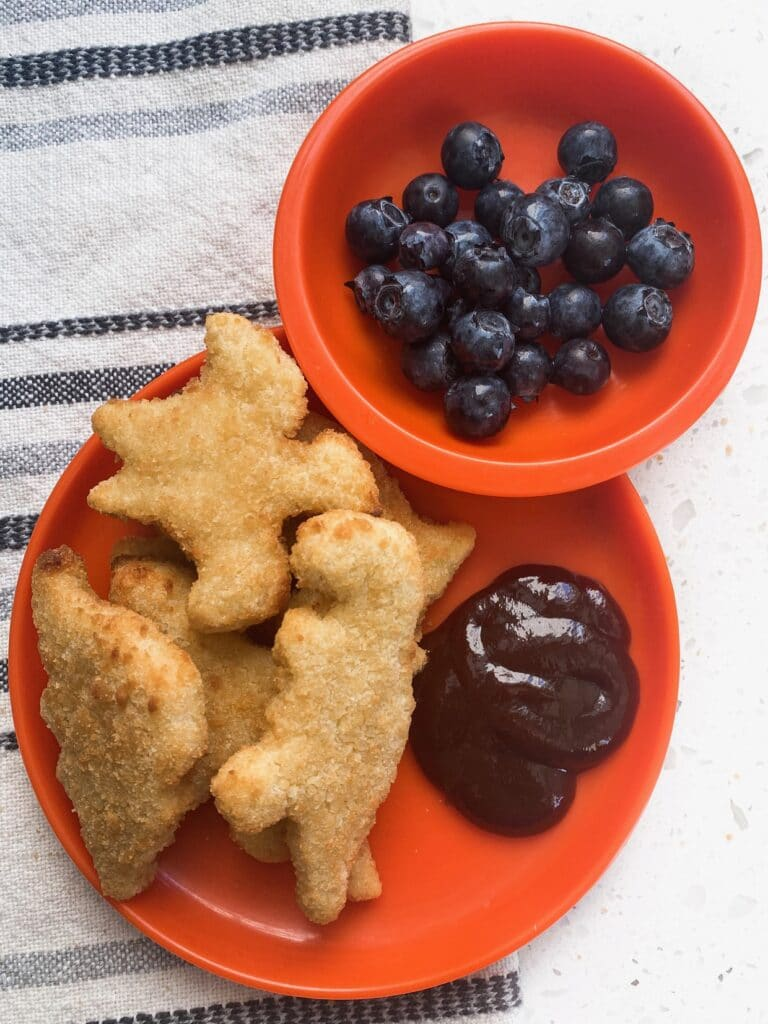 blueberries, bbq sauce, and chicken nuggets on an orange plate