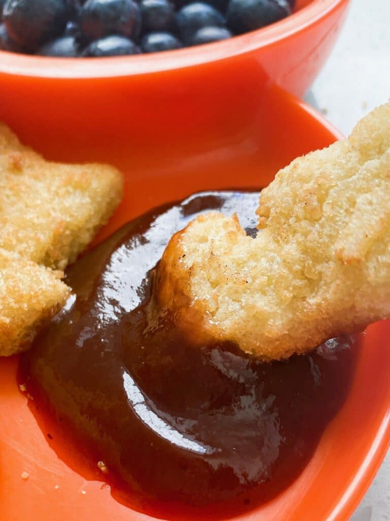 dino chicken nugget being dipped in ketchup