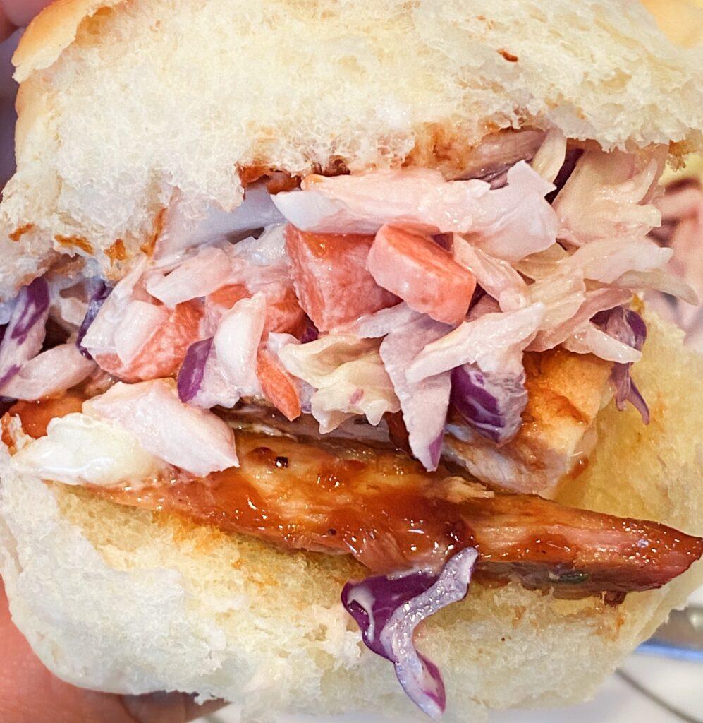 handheld coleslaw and bbq chicken slider on hawaiian roll