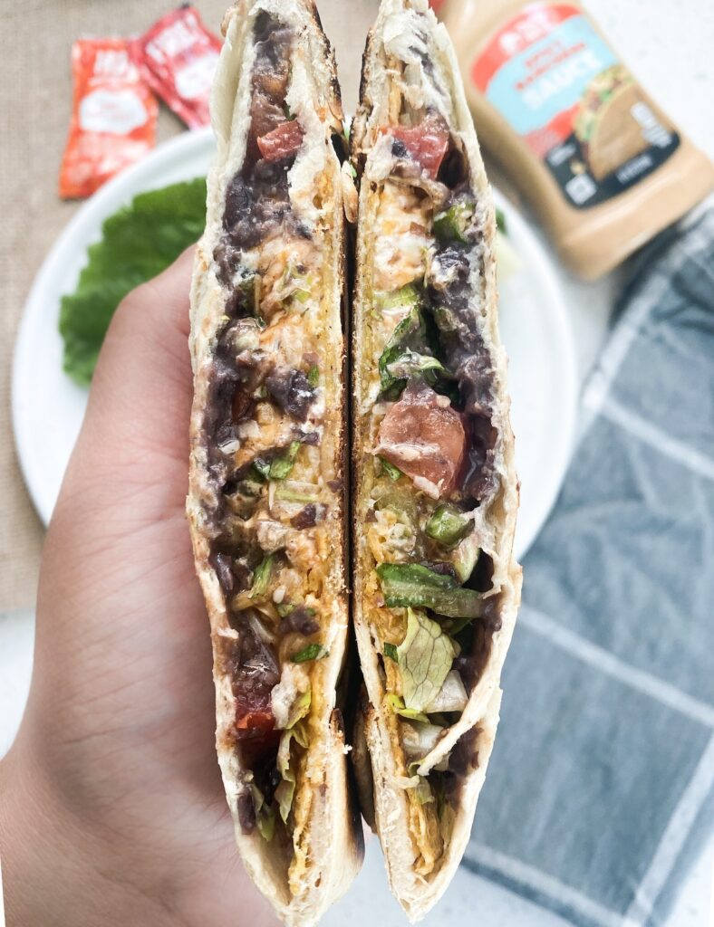 inside of a crunchwrap supreme being held in one hand.