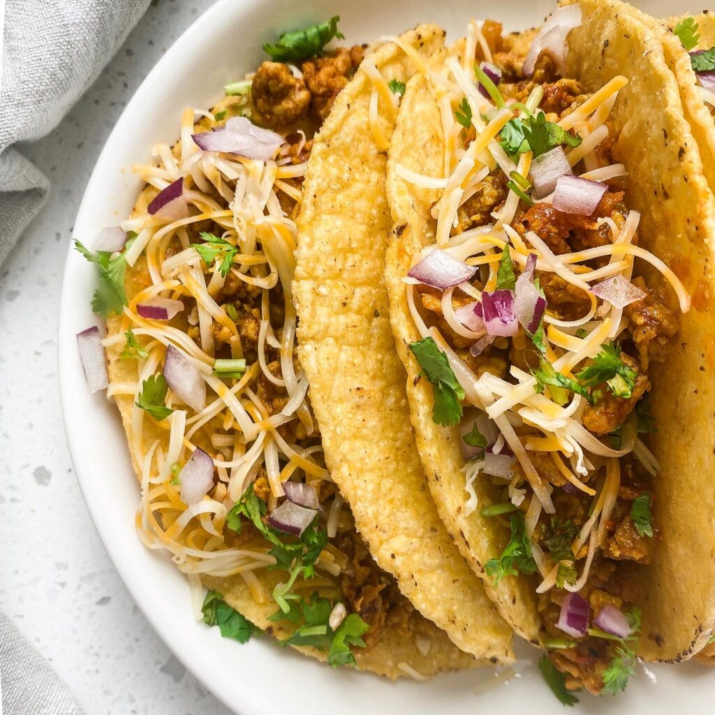 ground chicken indian tacos hard on a round pate