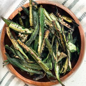 crispy okra fries made in an air fryer displayed in a round wooden bowl