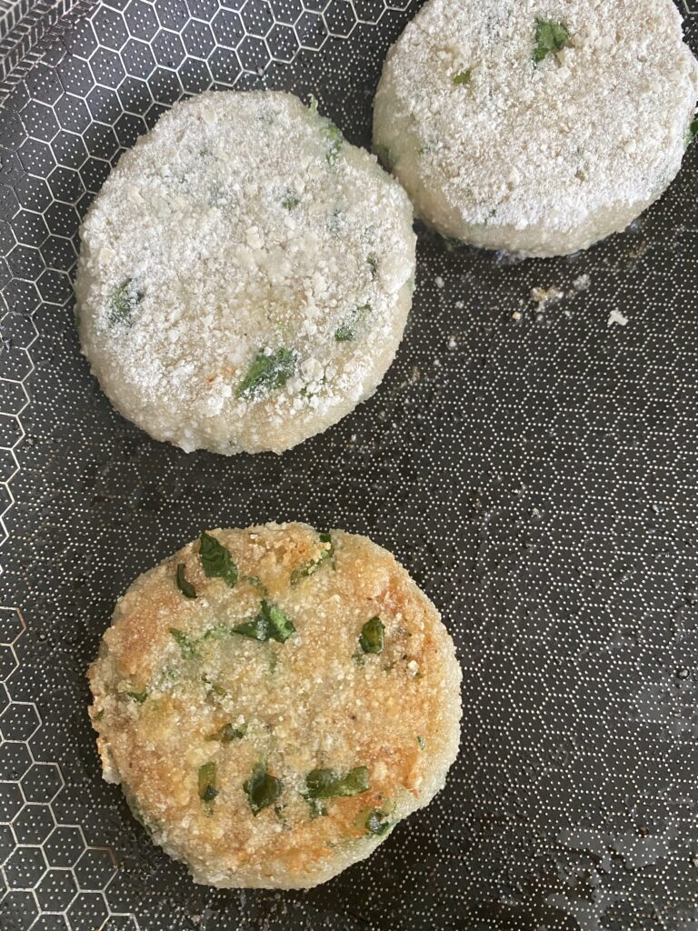 three aloo tikki in a pan and one is flipped over to show crisp brown color