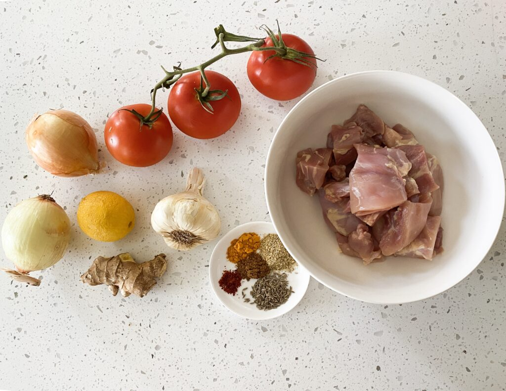 ingredients for desi chicken tapelu chicken on a counter tomatoes onions garlic ginger and raw chicken