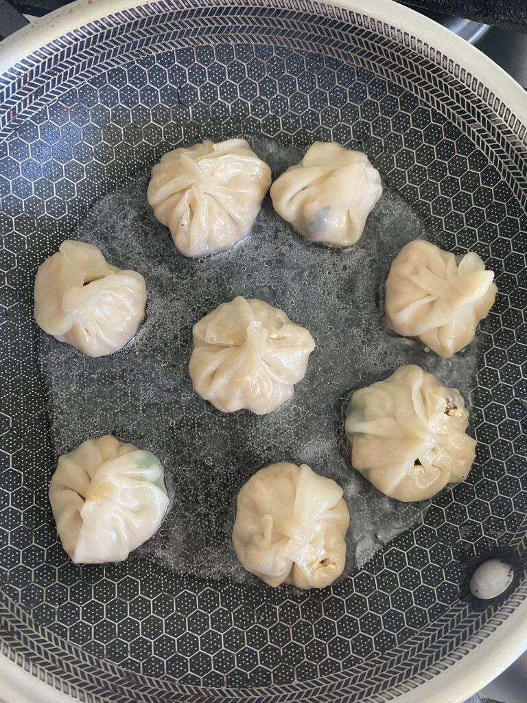 momos cooked in a pan with water