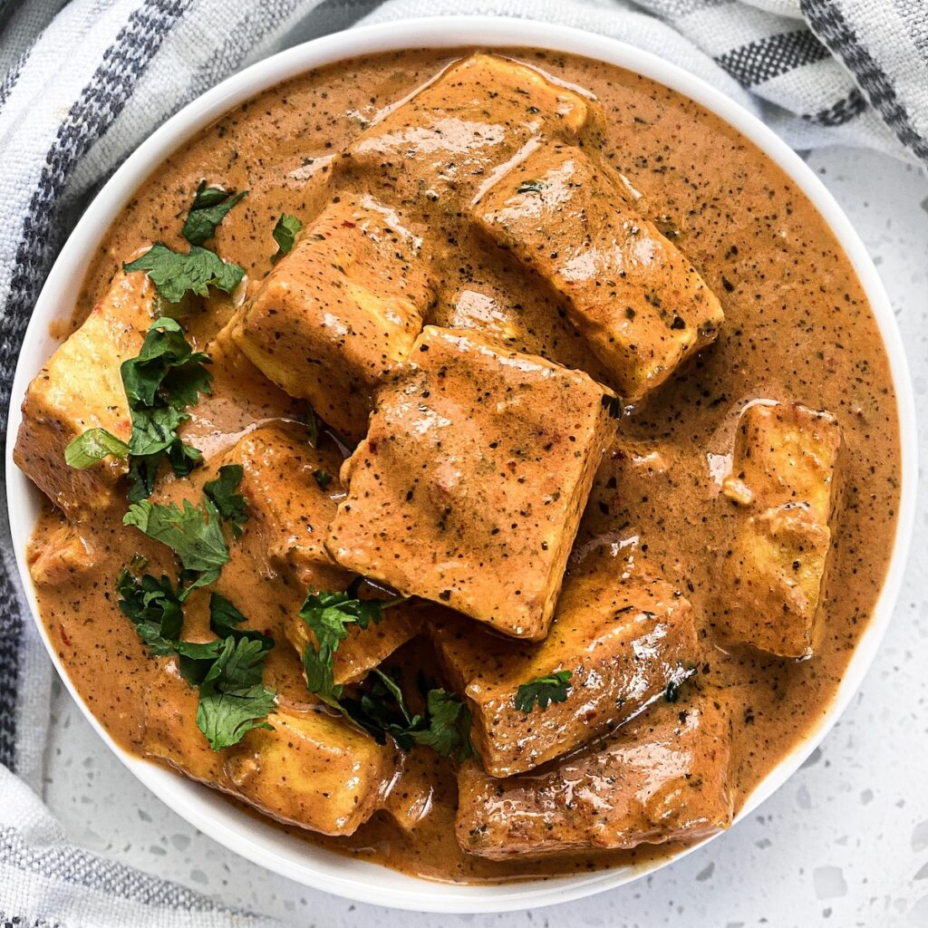 paneer butter masala in a round bowl with cilantro on the edge