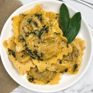 a bowl full of ravioli with sage butter on top