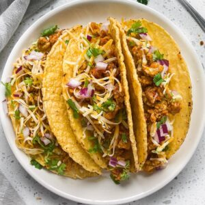 keema chicken tacos in hard shells three of them in a round plate with cilantro on top