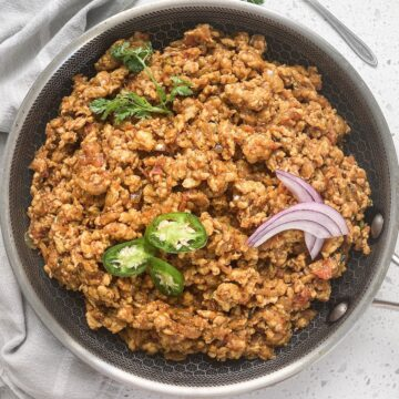 chicken kheema chicken keema recipe in a bowl with peppers, onions, and cilantro on top